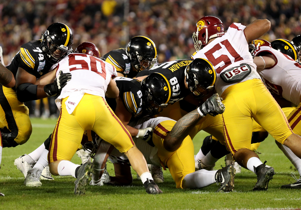 Iowa Hawkeyes offensive lineman Tyler Linderbaum (65) leads the way for quarterback Nate Stanley (4) against USC in the Holiday Bowl Friday, December 27, 2019 at San Diego Community Credit Union Stadium.  (Brian Ray/hawkeyesports.com)