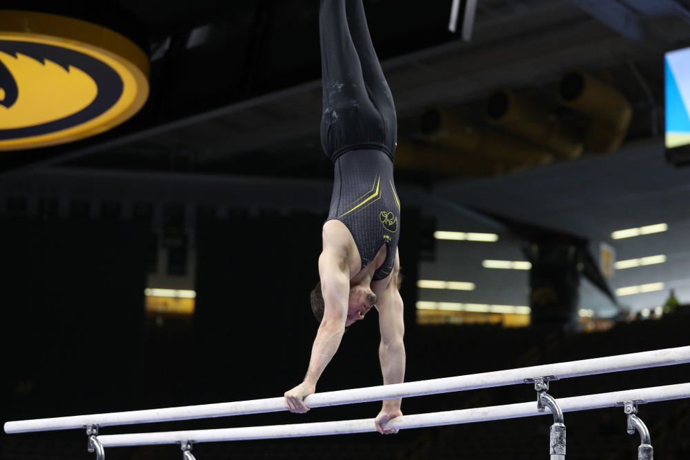 Iowa's Rogelio Vazquez competes on the parallel bars against the Ohio State Buckeyes  Saturday, March 16, 2019 at Carver-Hawkeye Arena.  (Brian Ray/hawkeyesports.com)