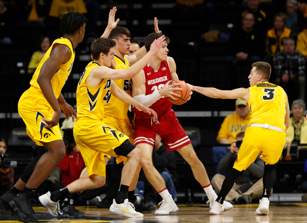 Iowa Hawkeyes forward Nicholas Baer (51), forward Luka Garza (55), and guard Jordan Bohannon (3)