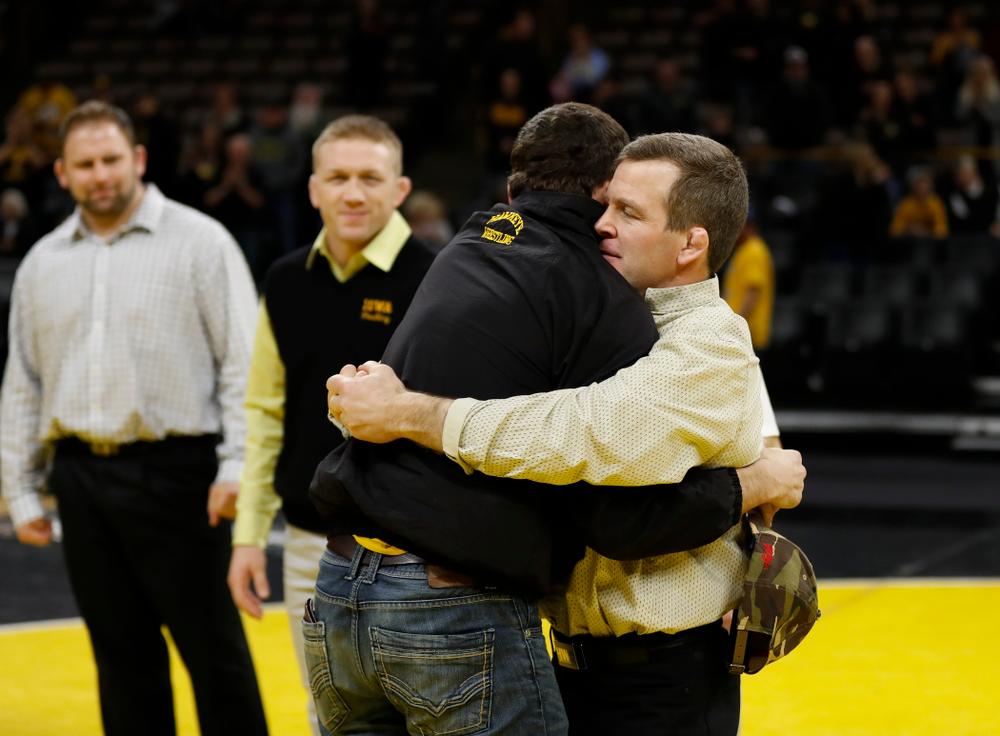 Iowa senior Logan McQuillen hugs associate head coach Terry Brands following their meet against Northwestern