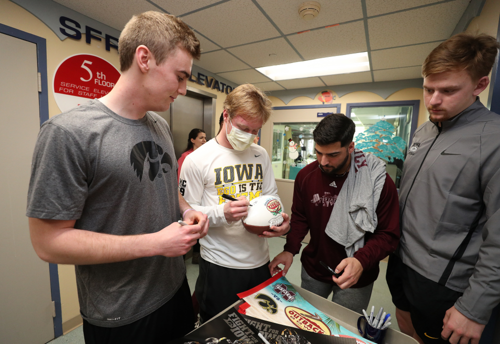 Iowa Hawkeyes punter Ryan Gersonde (2), wide receiver Max Cooper (19), and quarterback Spencer Petras (7) sign autographs for patients during a visit to Tampa General Hospital as part of the Outback Bowl Friday, December 28, 2018 in Tampa, FL.(Brian Ray/hawkeyesports.com)