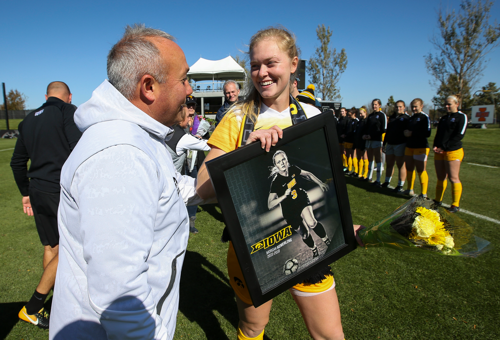 Iowa Hawkeyes head coach Dave DiIanni presents Iowa Hawkeyes defender Morgan Kemerling (3) with a framed photo during Senior Day ceremonies before a game against Northwestern at the Iowa Soccer Complex on October 21, 2018. (Tork Mason/hawkeyesports.com)