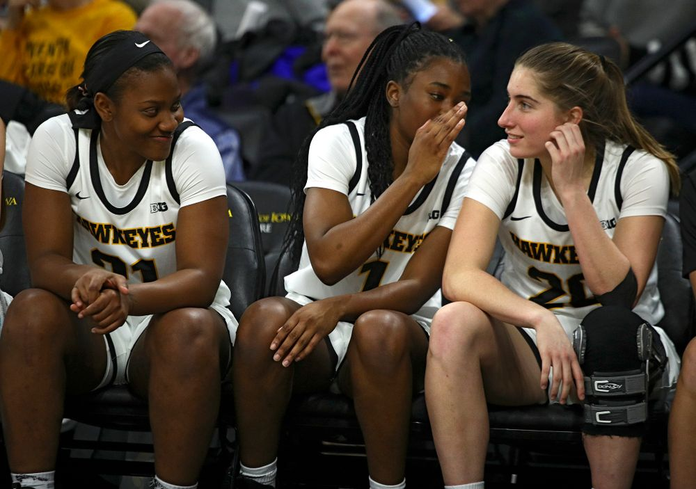 Iowa Hawkeyes guard Tomi Taiwo (1) whispers to guard Kate Martin (20) as she sits on the bench with guard Zion Sanders (21) during the fourth quarter of the game at Carver-Hawkeye Arena in Iowa City on Thursday, February 6, 2020. (Stephen Mally/hawkeyesports.com)
