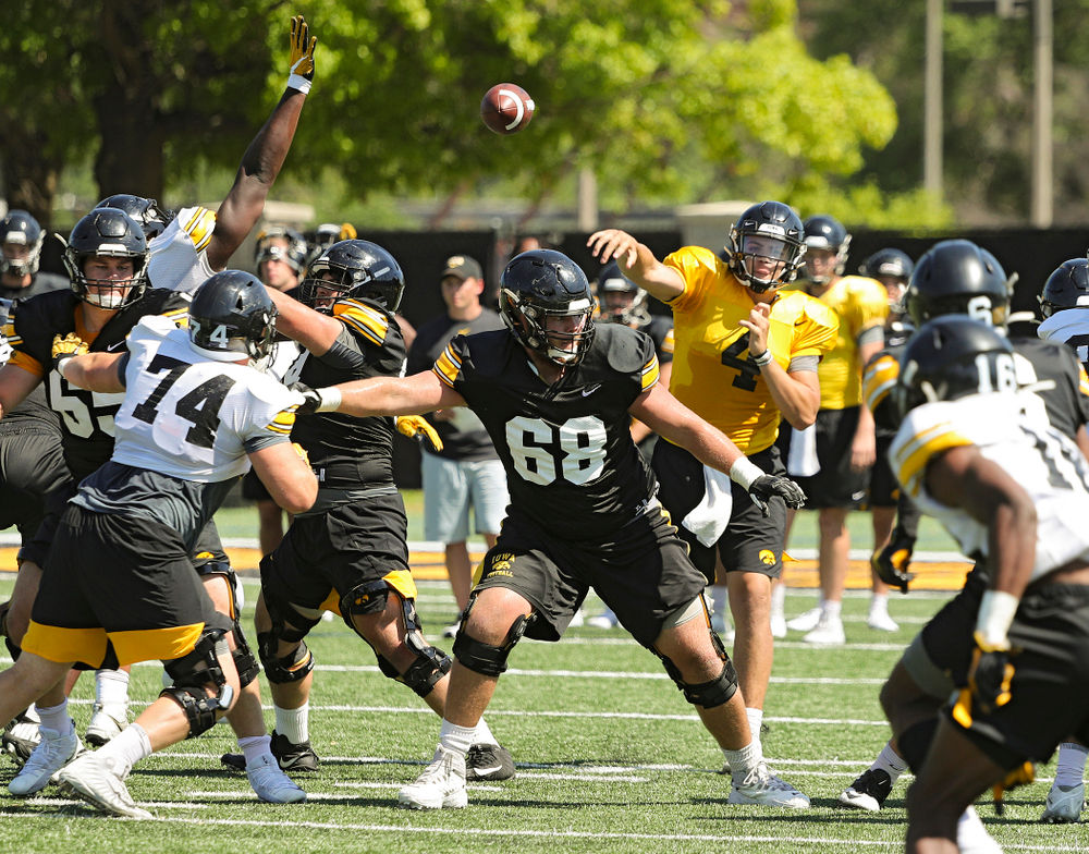 Iowa Hawkeyes quarterback Nate Stanley (4) throws a pass over defensive lineman Austin Schulte (74) and offensive lineman Landan Paulsen (68) during Fall Camp Practice No. 7 at the Hansen Football Performance Center in Iowa City on Friday, Aug 9, 2019. (Stephen Mally/hawkeyesports.com)
