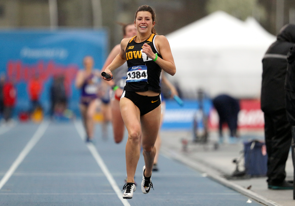 Iowa's Taylor Arco smiles as she nears the finish line while running the women's sprint medley relay event during the third day of the Drake Relays at Drake Stadium in Des Moines on Saturday, Apr. 27, 2019. (Stephen Mally/hawkeyesports.com)