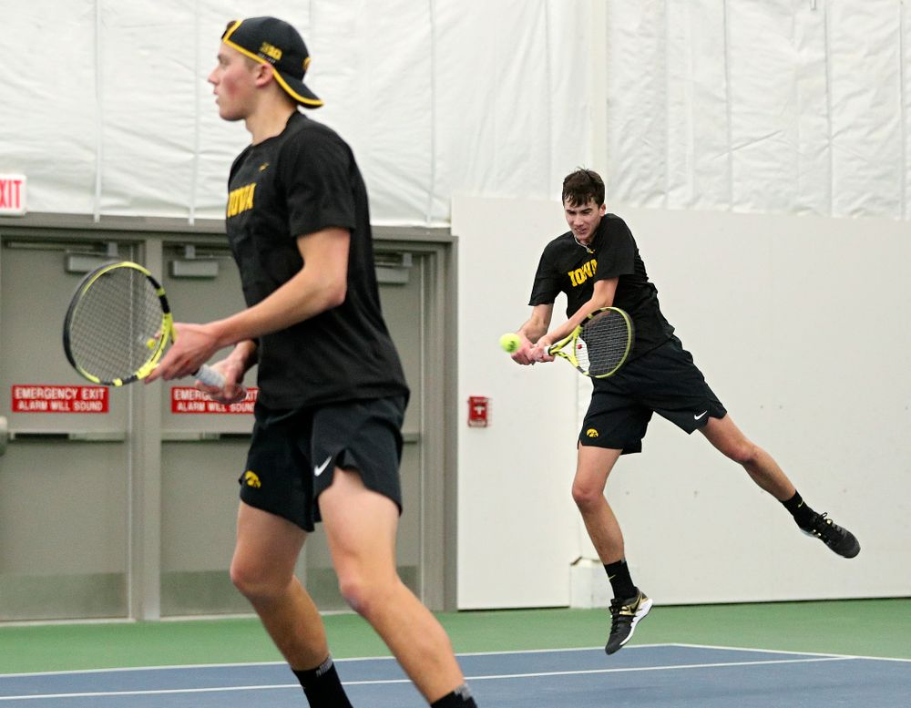 Iowa's Matt Clegg (right) returns a shot as Joe Tyler (left) looks on during their doubles match at the Hawkeye Tennis and Recreation Complex in Iowa City on Friday, February 14, 2020. (Stephen Mally/hawkeyesports.com)