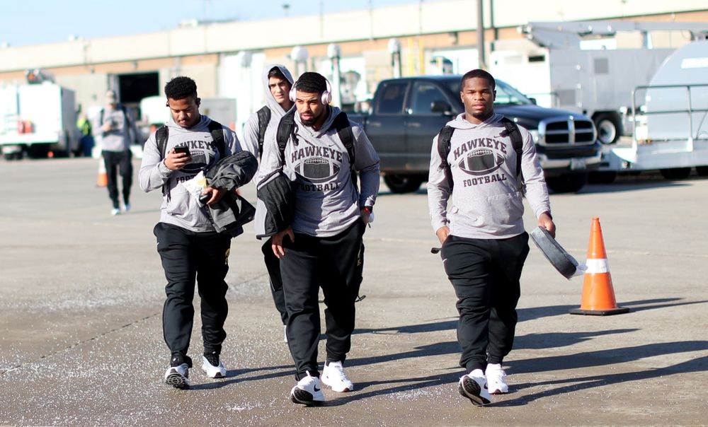 Iowa Hawkeyes running back Ivory Kelly-Martin (21), running back Toren Young (28), and running back Mekhi Sargent (10) board the team plane at the Eastern Iowa Airport Saturday, December 21, 2019 on the way to San Diego, CA for the Holiday Bowl. (Brian Ray/hawkeyesports.com)