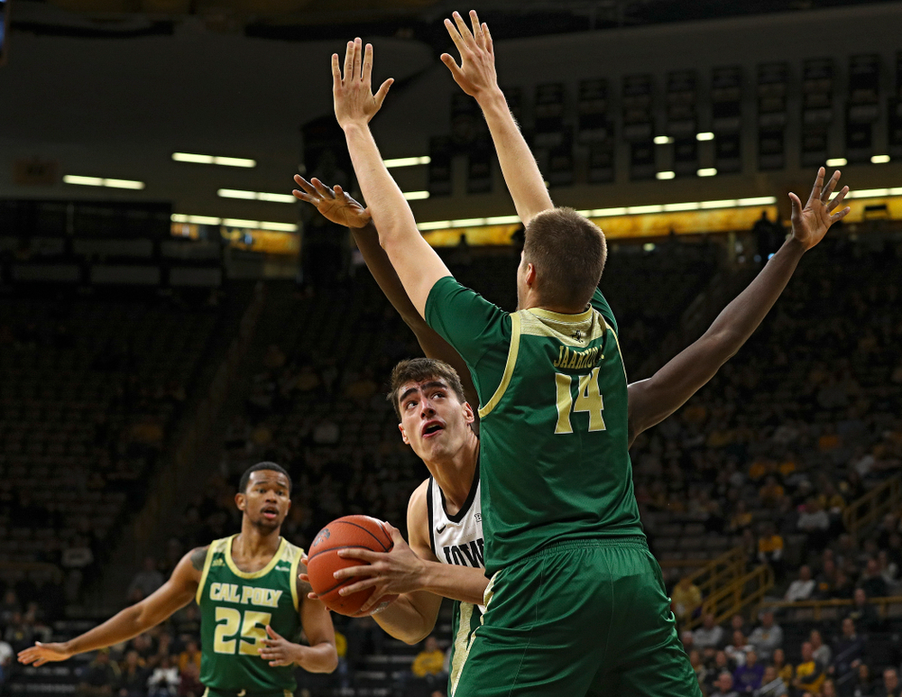 Iowa Hawkeyes center Luka Garza (55) eyes the basket around Cal Poly Mustangs forward Tuukka Jaakkola (14) during the first half of their game at Carver-Hawkeye Arena in Iowa City on Sunday, Nov 24, 2019. (Stephen Mally/hawkeyesports.com)
