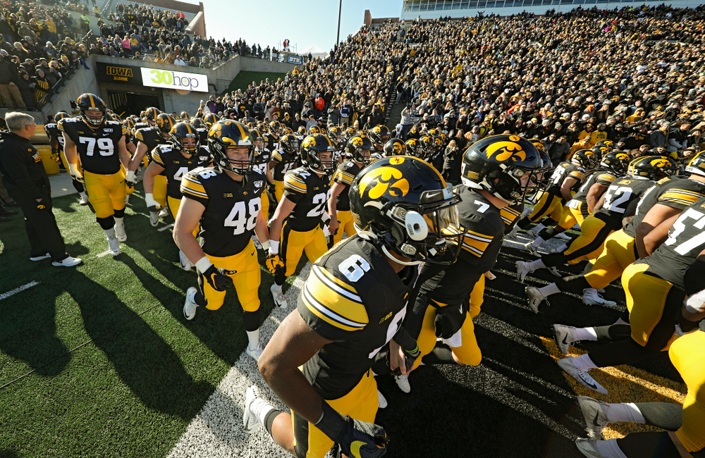 The Iowa Hawkeyes swarm as they take the field during halftime the game at Kinnick Stadium in Iowa City on Saturday, Nov 23, 2019. (Stephen Mally/hawkeyesports.com)