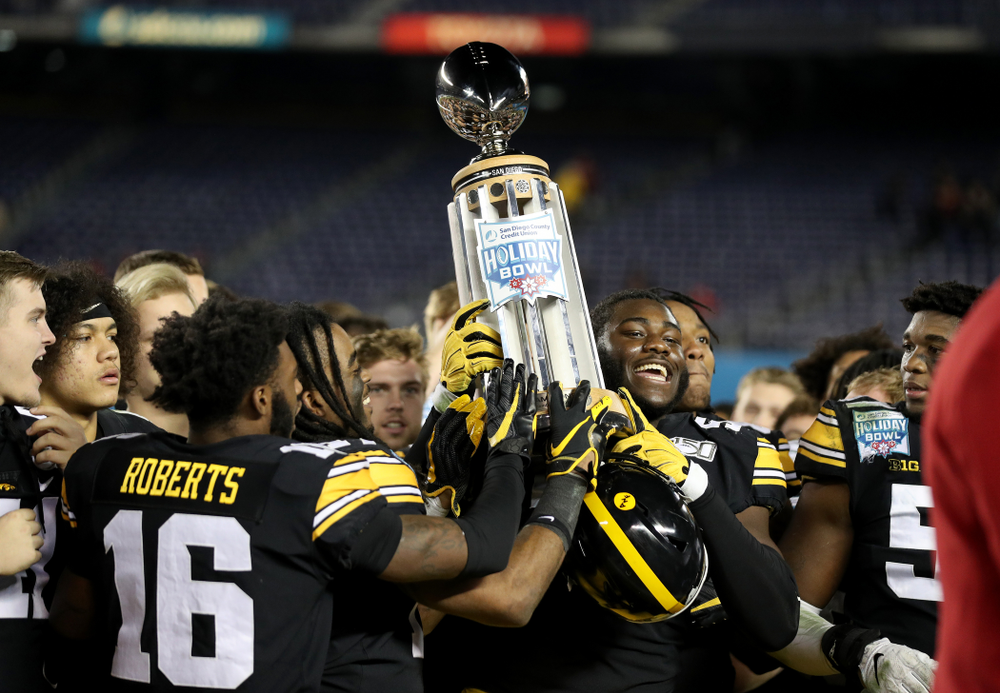 Iowa Hawkeyes defensive tackle Daviyon Nixon (54) holds the Holiday Bowl trophy following their win against USC in the Holiday Bowl Friday, December 27, 2019 at San Diego Community Credit Union Stadium.  (Brian Ray/hawkeyesports.com)