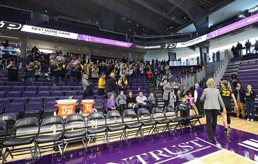 Iowa Hawkeyes fans wave to Iowa Hawkeyes head coach Lisa Bluder and guard Kathleen Doyle (22) as they walk off the court after winning their game at Welsh-Ryan Arena in Evanston, Ill. on Sunday, January 5, 2020. (Stephen Mally/hawkeyesports.com)