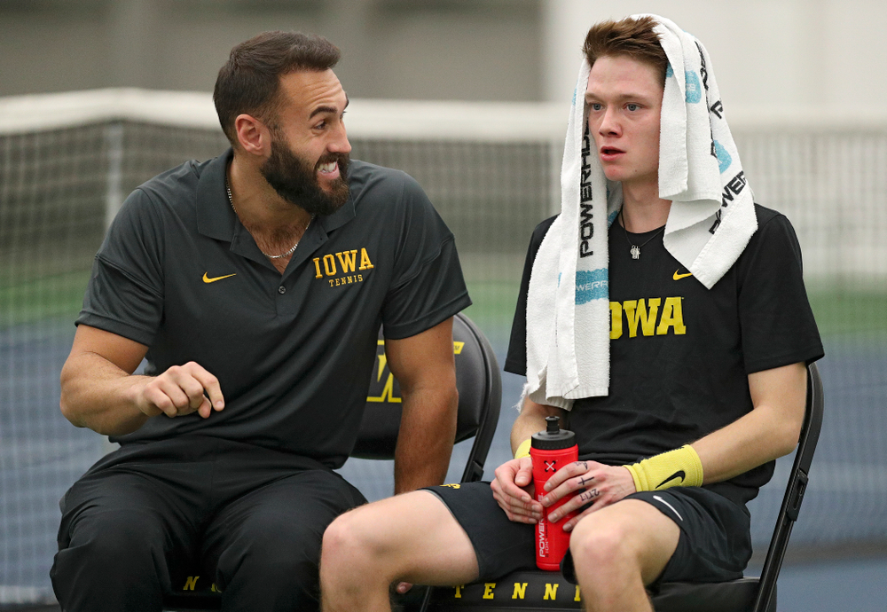 Iowa assistant coach Lloyd Bruce-Burgess (from left) talks with Jason Kerst during his match against Marquette at the Hawkeye Tennis and Recreation Complex in Iowa City on Saturday, January 25, 2020. (Stephen Mally/hawkeyesports.com)