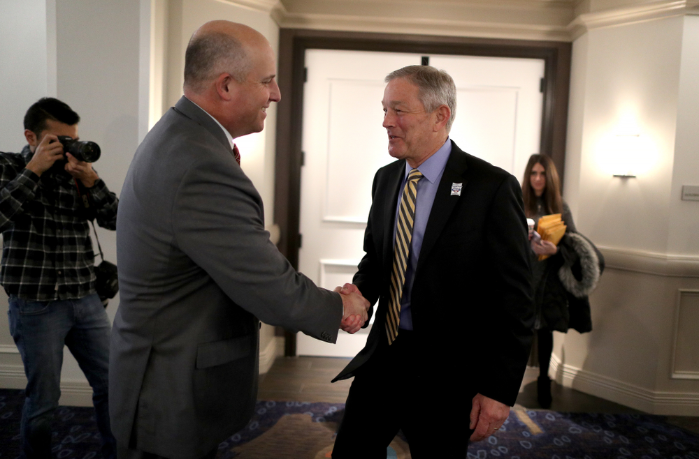 Iowa Hawkeyes head coach Kirk Ferentz shakes hands with USC head coach Clay Helton during a press conference leading up to the Holiday Bowl Thursday, December 26, 2019 in San Diego. (Brian Ray/hawkeyesports.com)