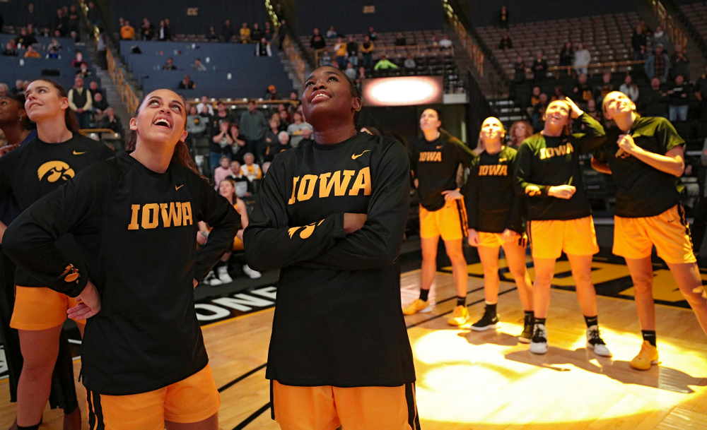 Iowa guard Gabbie Marshall (24) and guard Tomi Taiwo (1) watch the video board before their game against Winona State at Carver-Hawkeye Arena in Iowa City on Sunday, Nov 3, 2019. (Stephen Mally/hawkeyesports.com)
