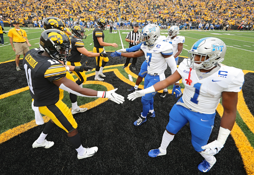 Iowa Hawkeyes captains defensive back Michael Ojemudia (11), linebacker Kristian Welch (34), fullback Brady Ross (36), and quarterback Nate Stanley (4) shake hands with the Middle Tennessee State captains before their game at Kinnick Stadium in Iowa City on Saturday, Sep 28, 2019. (Stephen Mally/hawkeyesports.com)