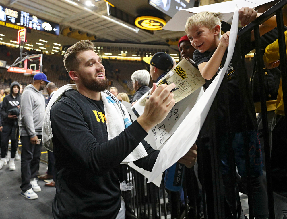 Iowa Hawkeyes guard Jordan Bohannon (3) autographs a poster for a young fan after winning their game at Carver-Hawkeye Arena in Iowa City on Friday, Nov 8, 2019. (Stephen Mally/hawkeyesports.com)