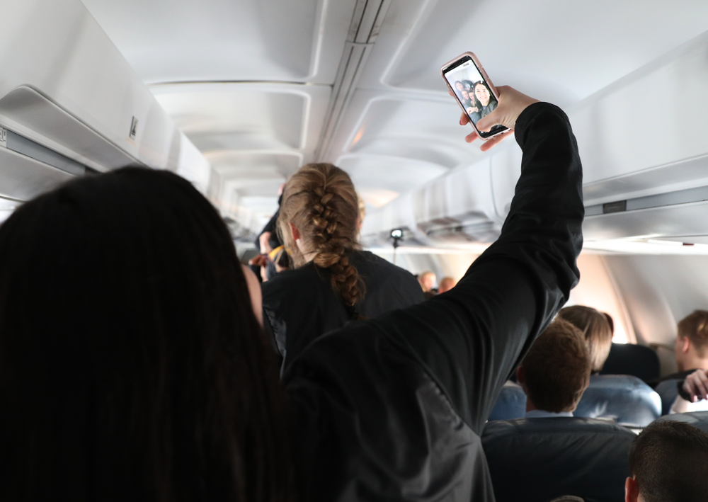 Iowa Hawkeyes forward Megan Gustafson (10) takes selfies with the band and spirit squad on board the team plane to Greensboro, NC for the Regionals of the 2019 NCAA Women's Basketball Championships Thursday, March 28, 2019 at the Eastern Iowa Airport. (Brian Ray/hawkeyesports.com)