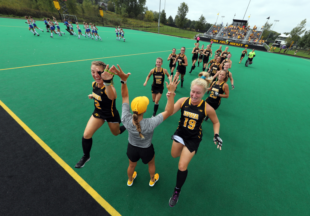 Iowa Hawkeyes defenseman Emily Deuell (2) and forward Ryley Miller (19) slap hands with assistant coach Roz Ellis before their game against the Duke Blue Devils Sunday, September 15, 2019 at Grant Field.  (Brian Ray/hawkeyesports.com)