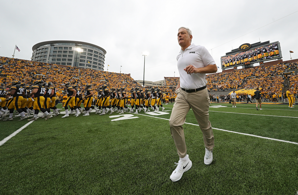 Iowa Hawkeyes head coach Kirk Ferentz runs onto the field as the Hawkeyes swarm as they take the field before their game at Kinnick Stadium in Iowa City on Saturday, Sep 28, 2019. (Stephen Mally/hawkeyesports.com)