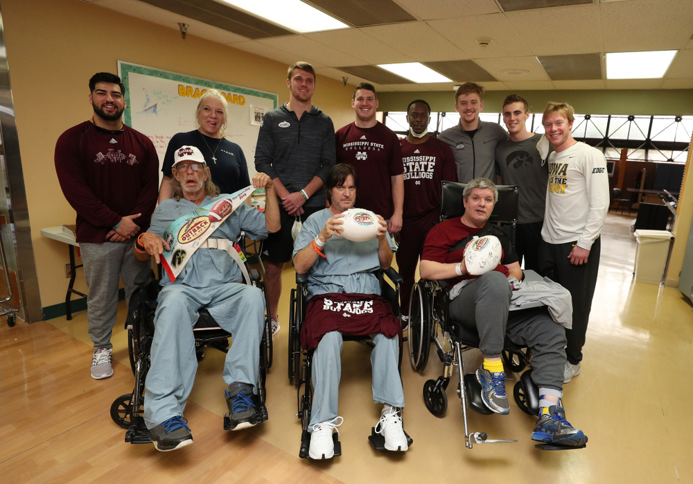 Iowa Hawkeyes quarterback Spencer Petras (7), punter Ryan Gersonde (2), and wide receiver Max Cooper (19) pose for photos with players from Mississippi State during a visit to Tampa General Hospital as part of the Outback Bowl Friday, December 28, 2018 in Tampa, FL.(Brian Ray/hawkeyesports.com)