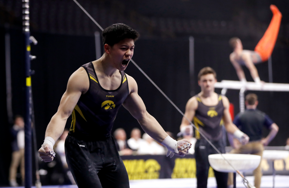 Bennet Huang competes on the high bar against Illinois