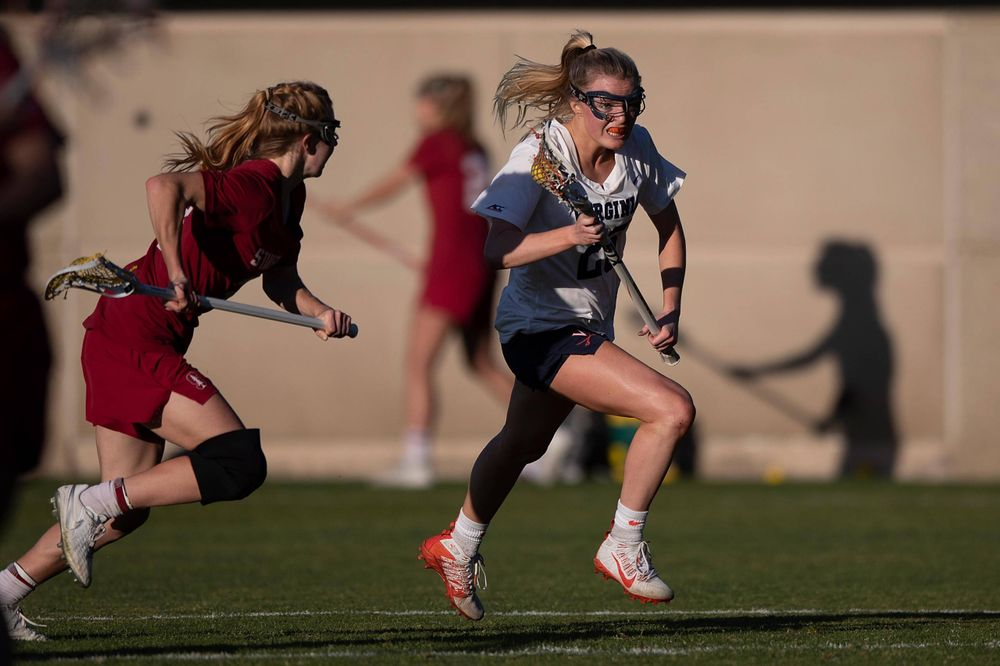 STANFORD, California - FEBRUARY 14: Virginia Cavaliers midfield Courtlynne Caskin (25) is defended by Stanford Cardinal midfield Jacie Lemos (33) during the second half at Cagan Stadium on February 14, 2020 in Stanford, California. The Virginia Cavaliers defeated the Stanford Cardinal 12-11. (Photo by Jason O. Watson)