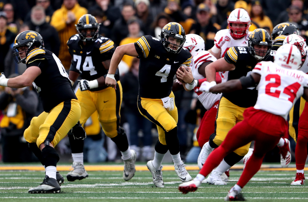 Iowa Hawkeyes quarterback Nate Stanley (4) picks up a first down against the Nebraska Cornhuskers Friday, November 23, 2018 at Kinnick Stadium. (Brian Ray/hawkeyesports.com)