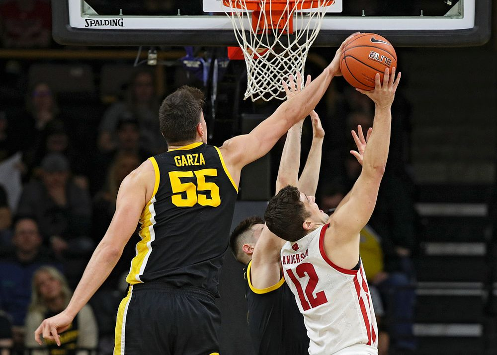 Iowa Hawkeyes center Luka Garza (55) blocks a shot by Wisconsin Badgers guard Trevor Anderson (12) during the first half of their game at Carver-Hawkeye Arena in Iowa City on Monday, January 27, 2020. (Stephen Mally/hawkeyesports.com)
