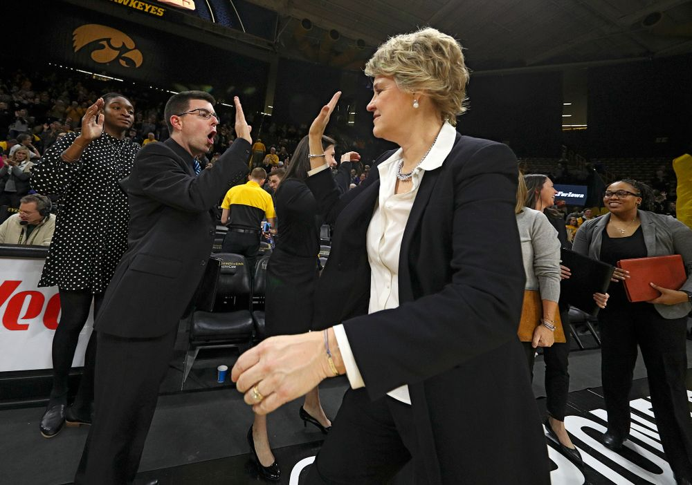 Iowa Hawkeyes head coach Lisa Bluder (right) gets a high-five from Ryan Gruebel, video coordinator and creative director, after winning their game at Carver-Hawkeye Arena in Iowa City on Thursday, January 23, 2020. (Stephen Mally/hawkeyesports.com)
