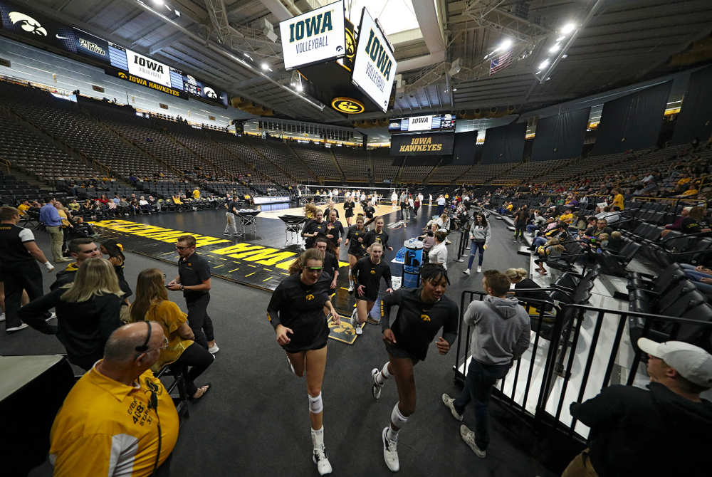The Iowa Hawkeyes run off the court after warming up before their match at Carver-Hawkeye Arena in Iowa City on Sunday, Oct 20, 2019. (Stephen Mally/hawkeyesports.com)