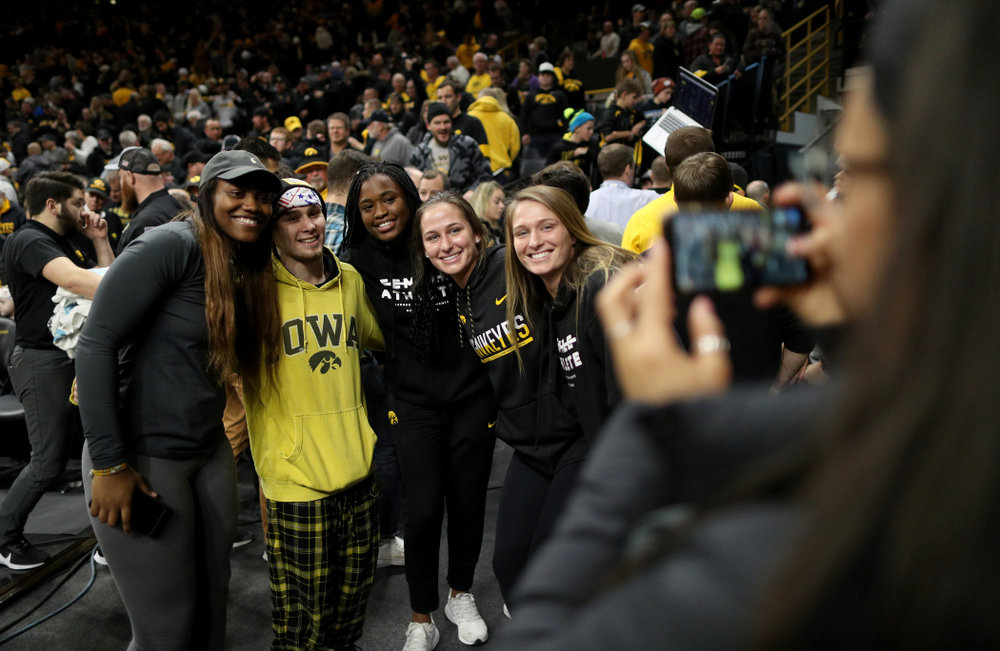 Iowa's Spencer Lee takes photos with members of the Iowa Women's Basketball team following their meet against Penn State Friday, January 31, 2020 at Carver-Hawkeye Arena. (Brian Ray/hawkeyesports.com)