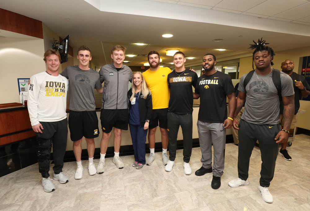 Iowa Hawkeyes tight end Ben Subbert (81), punter Ryan Gersonde (2), wide receiver Max Cooper (19), wide receiver Blair Brooks (83), quarterback Spencer Petras (7), linebacker Jayden McDonald (25), and defensive back Dallas Craddieth (15) pose for a photo with a nurse from Iowa during a visit to Tampa General Hospital as part of the Outback Bowl Friday, December 28, 2018 in Tampa, FL.(Brian Ray/hawkeyesports.com)