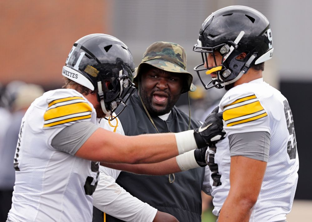 Iowa Hawkeyes defensive line coach Kelvin Bell (center) talks with defensive lineman Brady Reiff (91) and defensive end A.J. Epenesa (94) during Fall Camp Practice No. 15 at the Hansen Football Performance Center in Iowa City on Monday, Aug 19, 2019. (Stephen Mally/hawkeyesports.com)