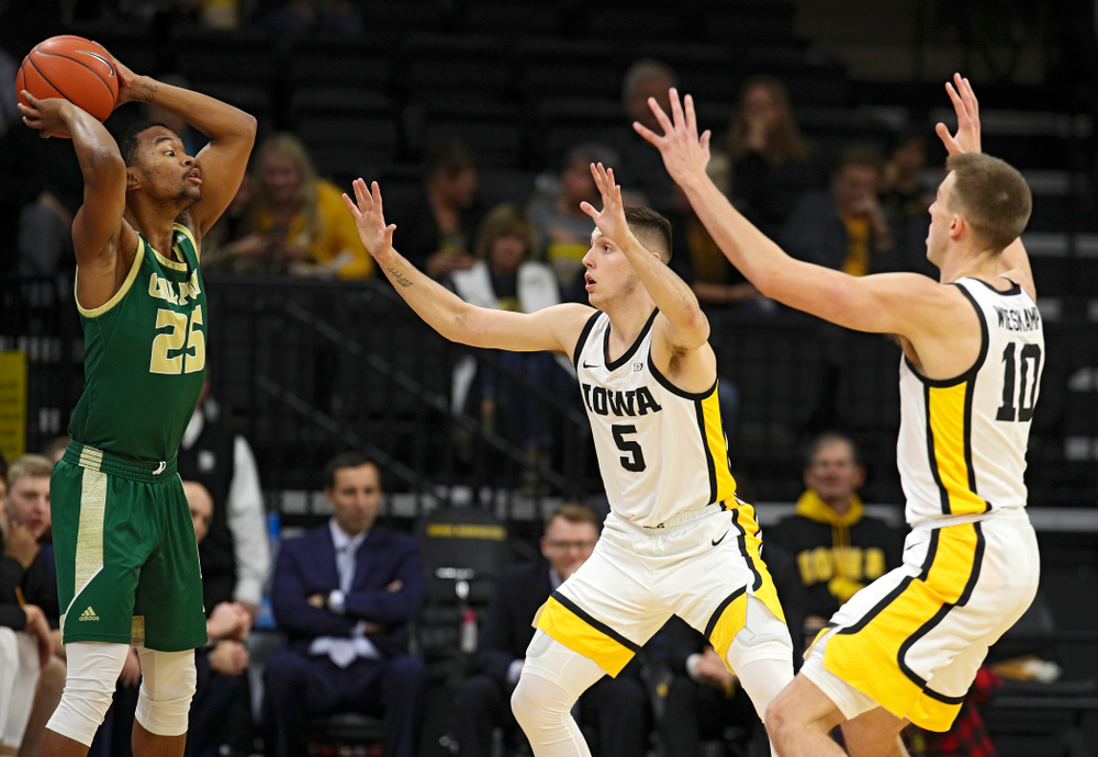 Iowa Hawkeyes guard CJ Fredrick (5) and guard Joe Wieskamp (10) pressure Cal Poly Mustangs guard Jamal Smith (25) during the first half of their game at Carver-Hawkeye Arena in Iowa City on Sunday, Nov 24, 2019. (Stephen Mally/hawkeyesports.com)
