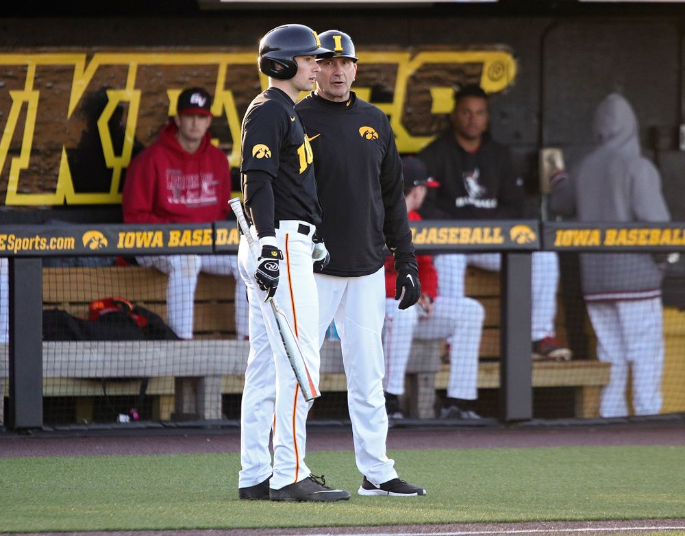 Iowa outfielder Ben Norman (9) talks with head coach Rick Heller before his at bat during the third inning of their game at Duane Banks Field in Iowa City on Tuesday, March 3, 2020. (Stephen Mally/hawkeyesports.com)