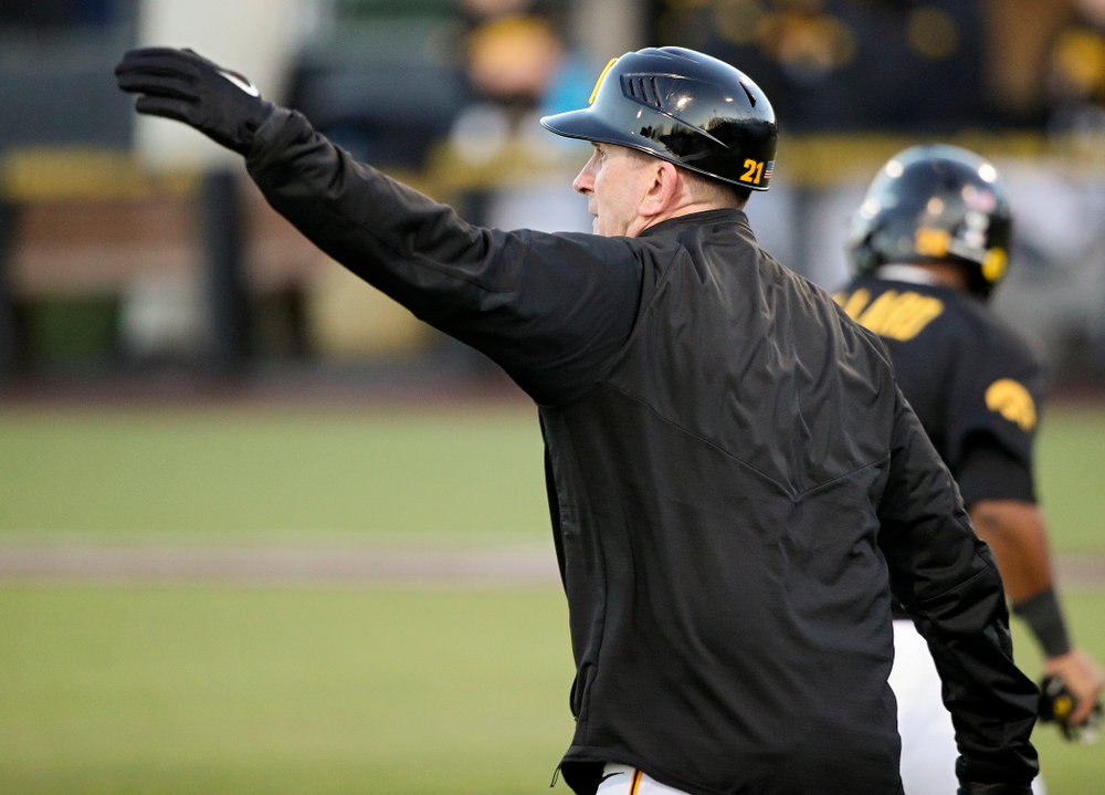 Iowa Hawkeyes head coach Rick Heller waves in runners during the fifth inning of their game at Duane Banks Field in Iowa City on Tuesday, March 3, 2020. (Stephen Mally/hawkeyesports.com)