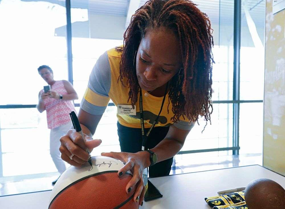 2019 University of Iowa Athletics Hall of Fame inductee Tangela Smith signs a basketball at the University of Iowa Athletics Hall of Fame in Iowa City on Friday, Aug 30, 2019. (Stephen Mally/hawkeyesports.com)