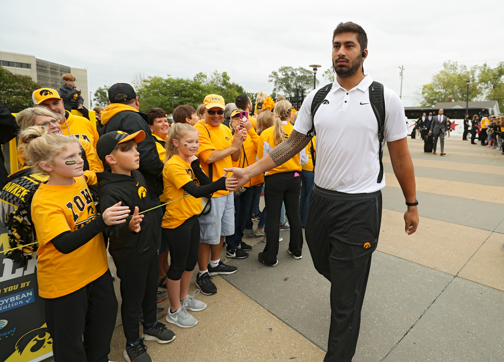 Iowa Hawkeyes defensive end A.J. Epenesa (94) gives high-fives to kids as he arrives with his team before their game at Kinnick Stadium in Iowa City on Saturday, Sep 28, 2019. (Stephen Mally/hawkeyesports.com)