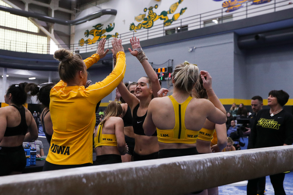 Allie Gilchrist (center) hjigh fives teammates during the Iowa women's gymnastics Black and Gold Intraquad Meet on Saturday, December 7, 2019 at the UI Field House. (Lily Smith/hawkeyesports.com)