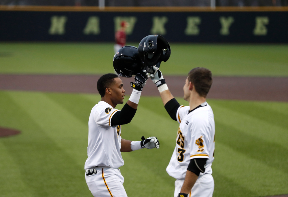 Iowa Hawkeyes third baseman Lorenzo Elion (1) celebrates with Kyle Crowl after hitting a home run against Coe College Wednesday, April 11, 2018 at Duane Banks Field. (Brian Ray/hawkeyesports.com)