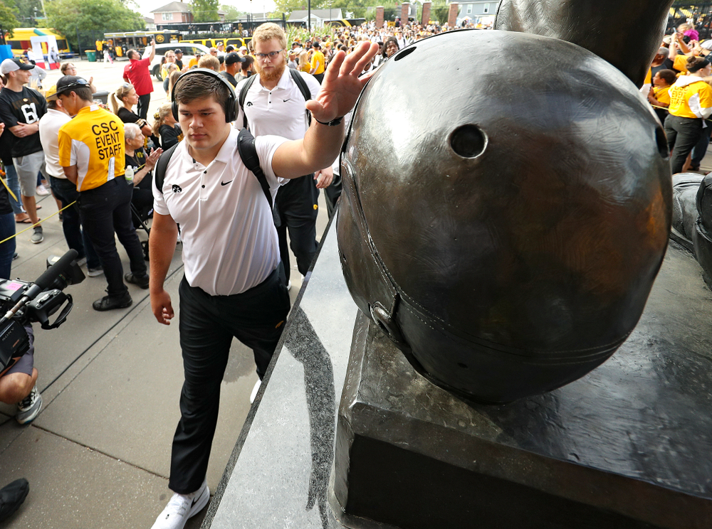 Iowa Hawkeyes offensive lineman Tyler Linderbaum (65) touches the helmet on the Nile Kinnick statue as the team arrives before their Big Ten Conference football game at Kinnick Stadium in Iowa City on Saturday, Sep 7, 2019. (Stephen Mally/hawkeyesports.com)