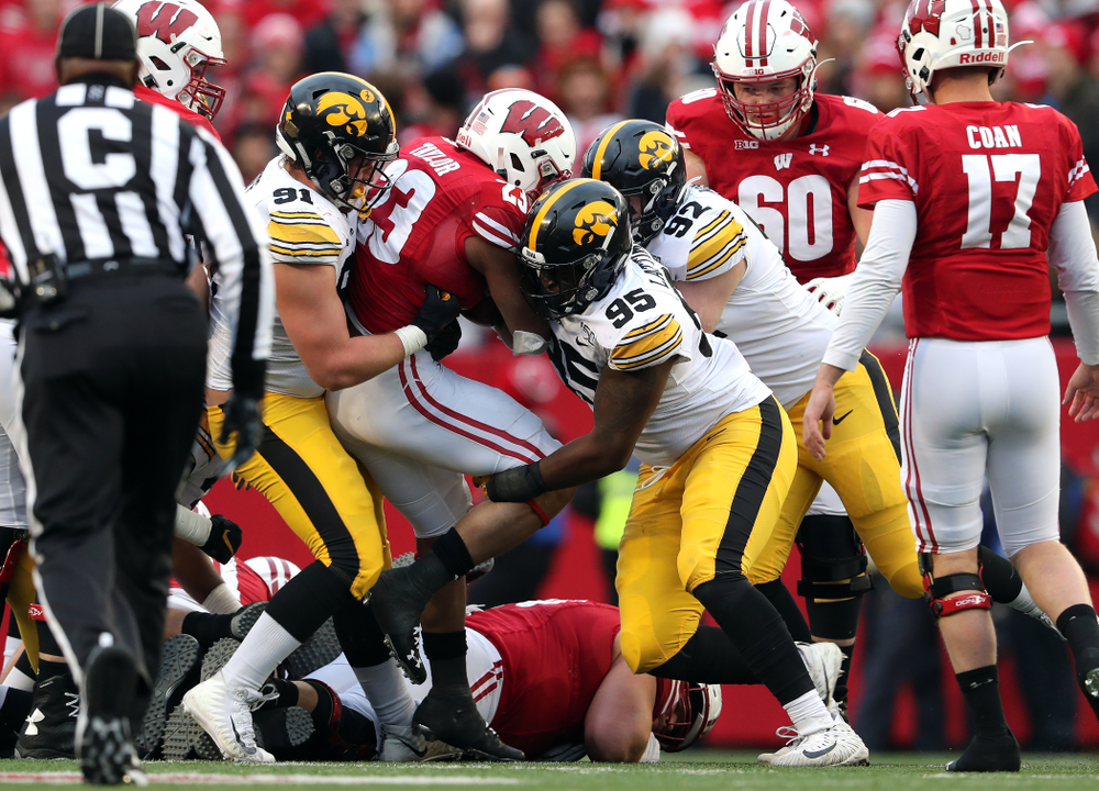 Iowa Hawkeyes defensive lineman Brady Reiff (91), defensive lineman Cedrick Lattimore (95), and defensive lineman John Waggoner (92) against the Wisconsin Badgers Saturday, November 9, 2019 at Camp Randall Stadium in Madison, Wisc. (Brian Ray/hawkeyesports.com)