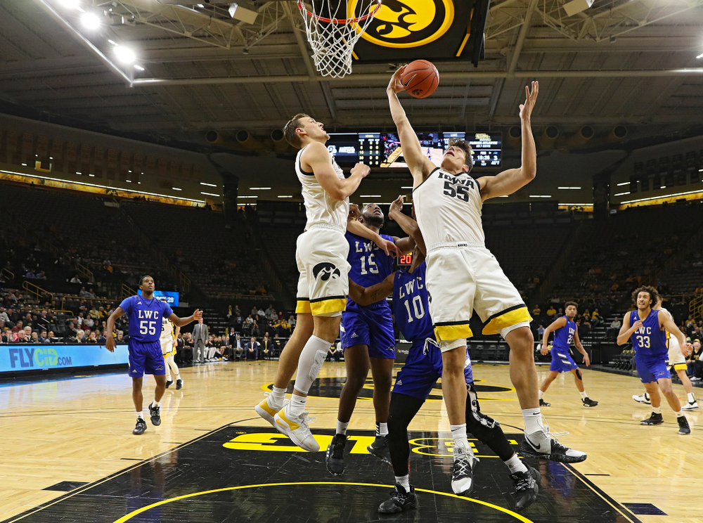 Iowa Hawkeyes center Luka Garza (55) pulls in an offensive rebound as forward Jack Nunge (left) looks on during the first half of their exhibition game against Lindsey Wilson College at Carver-Hawkeye Arena in Iowa City on Monday, Nov 4, 2019. (Stephen Mally/hawkeyesports.com)
