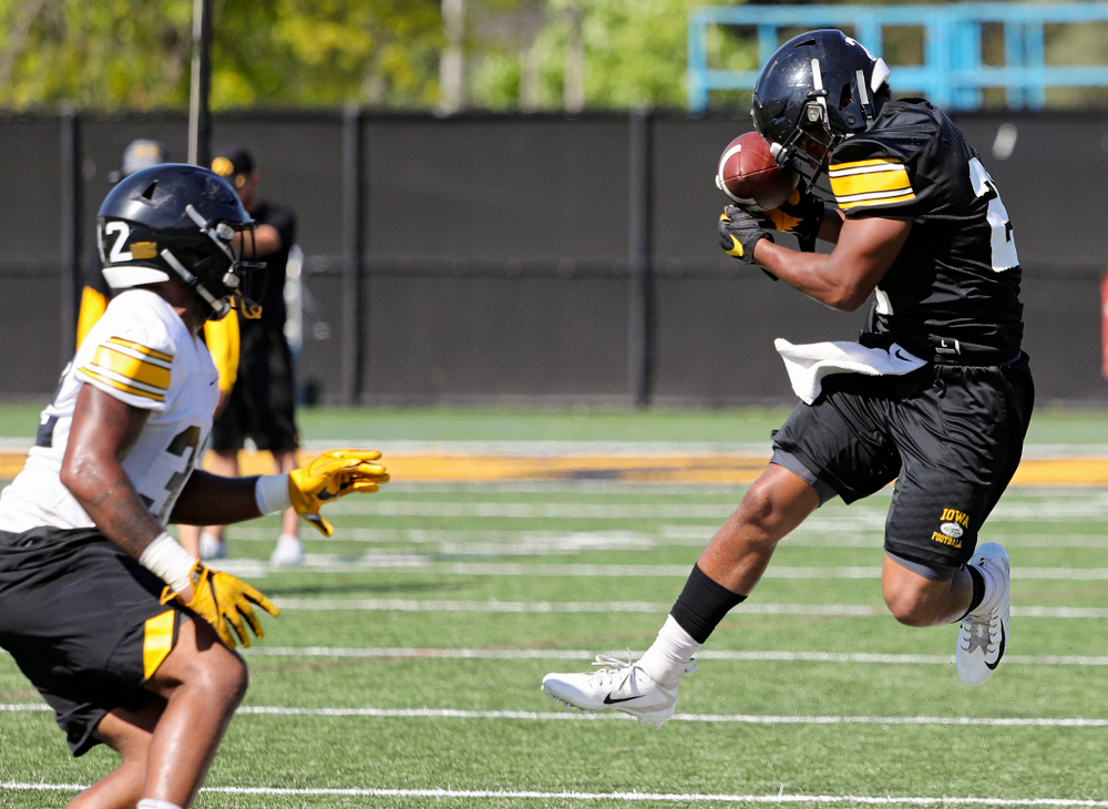 Iowa Hawkeyes running back Ivory Kelly-Martin (21) gathers in a pass against his helmet as linebacker Djimon Colbert (32) closes in during Fall Camp Practice No. 13 at the Hansen Football Performance Center in Iowa City on Friday, Aug 16, 2019. (Stephen Mally/hawkeyesports.com)