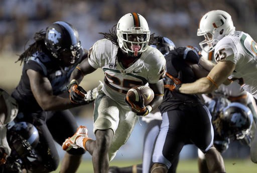 Miami's Dallas Crawford (25) carries the ball against North Carolina during the second half of an NCAA college football game in Chapel Hill, N.C.,...