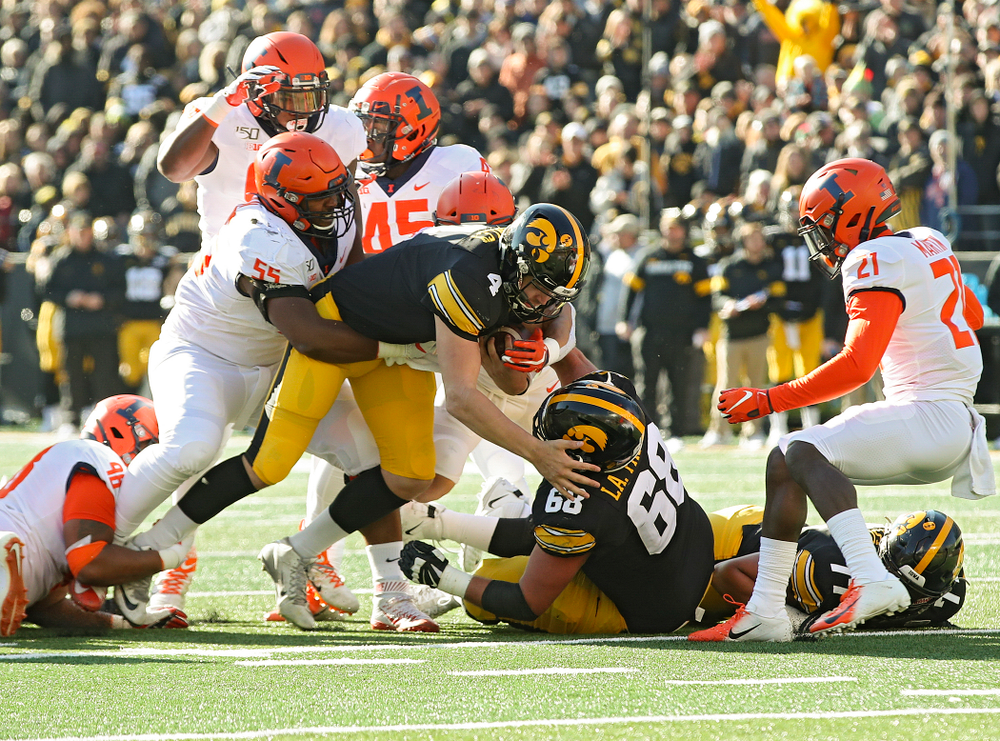 Iowa Hawkeyes quarterback Nate Stanley (4) runs for a first down during the second quarter of their game at Kinnick Stadium in Iowa City on Saturday, Nov 23, 2019. (Stephen Mally/hawkeyesports.com)