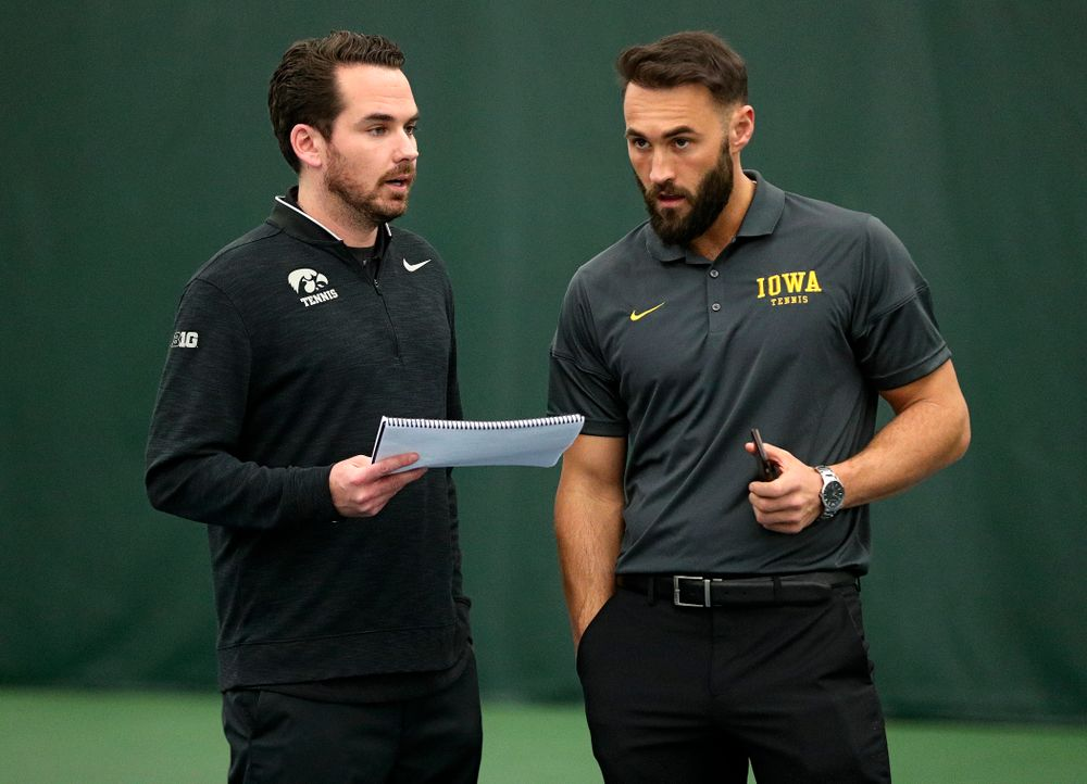 Mellecker Family Head Men's Tennis Coach Ross Wilson (from left) and assistant coach Lloyd Bruce-Burgess talk during a match at the Hawkeye Tennis and Recreation Complex in Iowa City on Friday, February 14, 2020. (Stephen Mally/hawkeyesports.com)