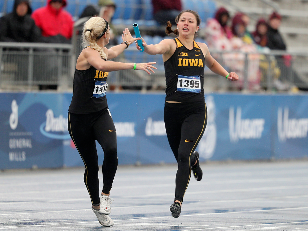 Iowa's Jenny Kimbro (right) hands the baton off to Aly Weum as they run the women's 1600 meter relay event during the third day of the Drake Relays at Drake Stadium in Des Moines on Saturday, Apr. 27, 2019. (Stephen Mally/hawkeyesports.com)
