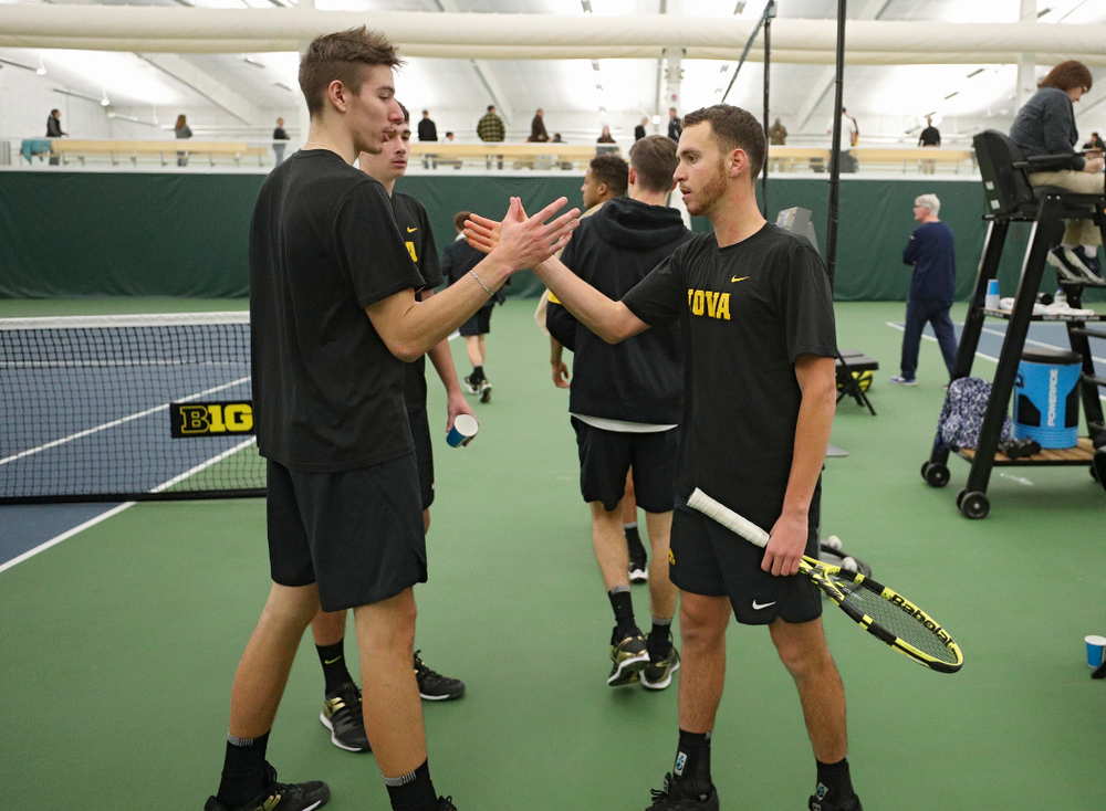 Iowa's Nikita Snezhko (from left) celebrates with Kareem Allaf after Allaf won his match against Marquette at the Hawkeye Tennis and Recreation Complex in Iowa City on Saturday, January 25, 2020. (Stephen Mally/hawkeyesports.com)
