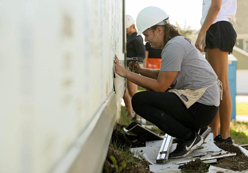 Iowa's Paula Valino Ramos hammers in a nail on a piece of siding as they work on a Habitat for Humanity Women Build project in Iowa City on Wednesday, Sep 25, 2019. (Stephen Mally/hawkeyesports.com)